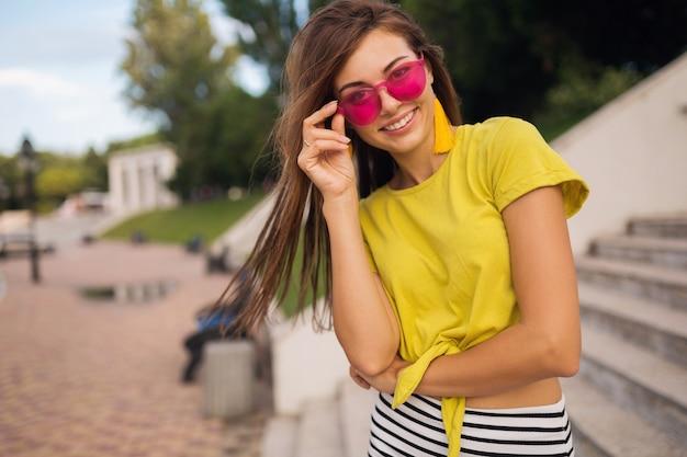 Portret van jonge aantrekkelijke lachende vrouw met plezier in stadspark, positief, gelukkig, gele top, oorbellen, roze zonnebril, zomer stijl modetrend, stijlvolle accessoires dragen