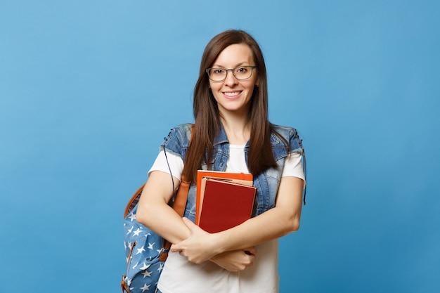 Portret van jonge aantrekkelijke lachende vrouw student in glazen met rugzak schoolboeken te houden en klaar om te leren geïsoleerd op blauwe achtergrond. onderwijs in het concept van de middelbare schooluniversiteit.
