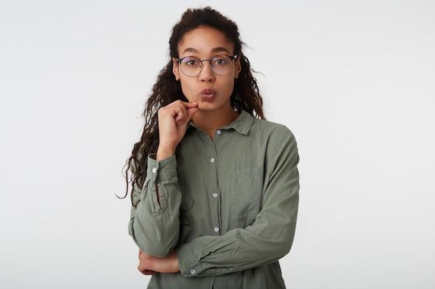 Portret van jonge aantrekkelijke langharige krullende brunette dame hand opheffen naar haar gezicht en lippen tuit terwijl ze naar de camera kijkt, staande op witte achtergrond