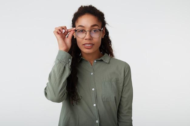 Portret van jonge aantrekkelijke langharige krullende dame met donkere huid die positief naar camera kijkt en opgeheven hand op brillen houdt, die zich op witte achtergrond bevindt