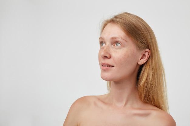 Portret van jonge aantrekkelijke positieve roodharige langharige dame die verwonderd kijkt en lichtjes glimlacht, die zich over witte muur met naakte schouders bevindt