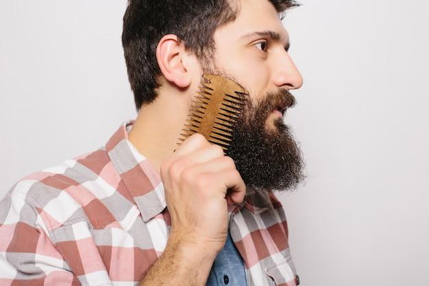 Portret van jonge aantrekkelijke roodharige hipster man met ernstige en zelfverzekerde blik, houten kam vasthouden en zijn dikke baard doen. stijlvolle bebaarde kapper in geruit overhemd kammen in salon. horizontaal