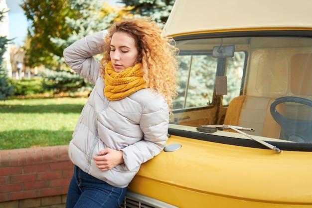 Portret van jonge aantrekkelijke roodharige krullende vrouw die voor gele auto blijft