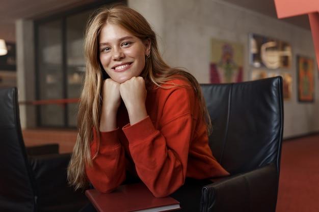Portret van jonge aantrekkelijke roodharige vrouwelijke student, zit op een leunstoel die op wapens leunt en glimlacht.