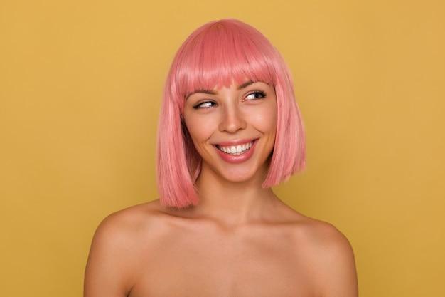 Portret van jonge aantrekkelijke roze harige vrouw die haar perfecte witte tanden toont terwijl ze vrolijk lacht, positief opzij kijkt terwijl ze over de mosterdmuur staat