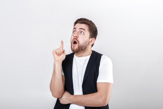 Portret van jonge aantrekkelijke verrast brunette man in wit overhemd op grijze achtergrond. verrassend feit