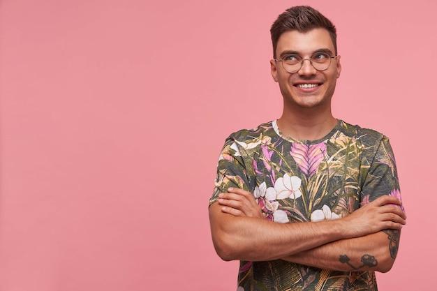 Portret van jonge aantrekkelijke vrolijke kerel in gebloemd overhemd, ziet er gelukkig uit, staat op roze achtergrond met kopie ruimte en glimlacht breed.