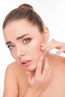 Portret van jonge aantrekkelijke vrouw die acne op haar gezicht zoekt