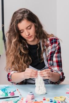 Portret van jonge aantrekkelijke vrouw die ambachtvoorwerp maken die witte klei gebruiken