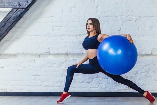 Portret van jonge aantrekkelijke vrouw die oefeningen doet