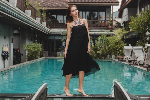 Portret van jonge aantrekkelijke vrouw in elegante jurk, strooien hoed, zomerstijl, modetrend, vakantie, glimlachen, stijlvolle accessoires, zonnebril, poseren op tropische villa op bali