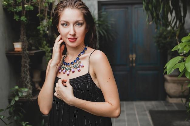 Portret van jonge aantrekkelijke vrouw in stijlvolle zwarte jurk poseren in tropische villa, sexy, elegante zomer stijl, modieuze ketting accessoires, glimlachen, sieraden, puur natuurlijke huid van gezicht