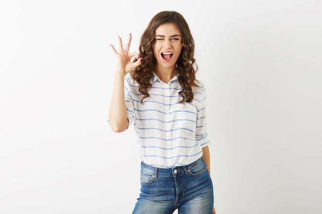Portret van jonge aantrekkelijke vrouw met opgewonden gezichtsuitdrukking die positief gebaar toont, glimlachen, gelukkig, knipogen, hipsterstijl, geïsoleerd, krullend haar, ok teken, vrolijke stemming, mooi gezicht