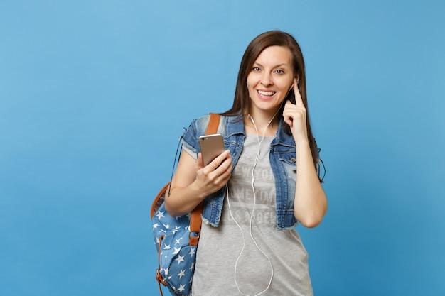 Portret van jonge aantrekkelijke vrouw student in denim kleding met rugzak, koptelefoon luisteren muziek houdt mobiele telefoon geïsoleerd op blauwe achtergrond. onderwijs op de universiteit. kopieer ruimte voor advertentie.