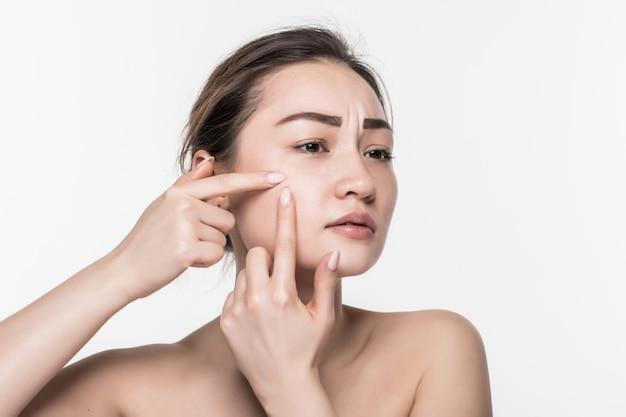 Portret van jonge aantrekkelijke vrouw wat betreft haar gezicht en het zoeken naar acne die op witte muur wordt geïsoleerd