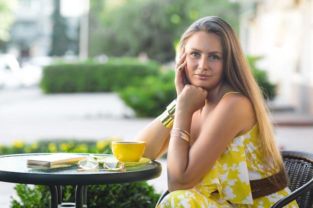 Portret van jonge aantrekkelijke vrouwenzitting bij het koffie met kop van koffie. dame die aromatische thee drinkt. beeld van mooi meisje bij de cafetaria die haar datum wacht.