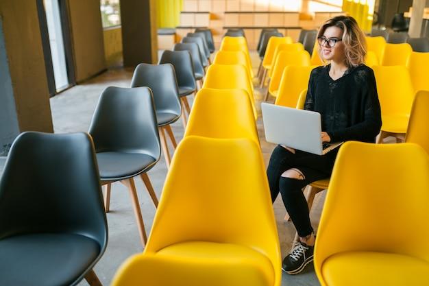 Portret van jonge aantrekkelijke vrouwenzitting in collegezaal die aan laptop werkt die glazen draagt, student die in klaslokaal met vele gele stoelen leert