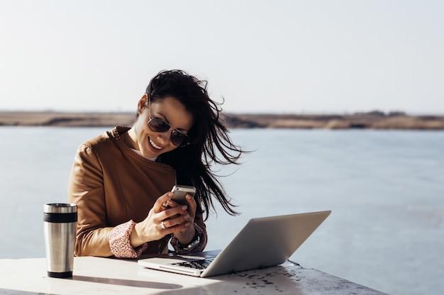 Portret van jonge aantrekkelijke zakenvrouw typen berichten op haar smartphone