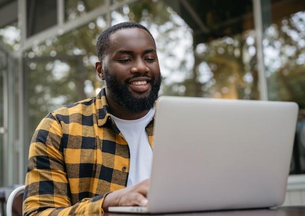 Portret van jonge afrikaanse amerikaanse programmeur die laptop computer met behulp van