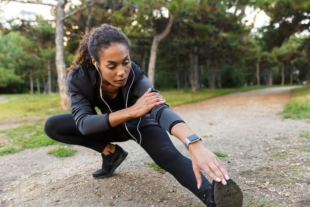 Portret van jonge afrikaanse amerikaanse vrouwen20s die zwart trainingspak dragen die oefeningen doen, en haar benen in groen park strekken