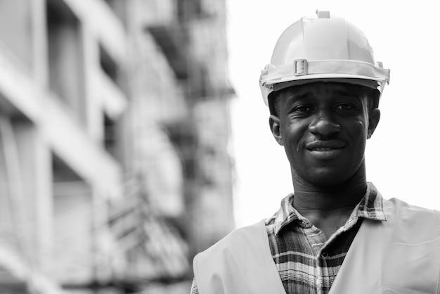 Portret van jonge afrikaanse man bouwvakker op de bouwplaats buiten in zwart-wit