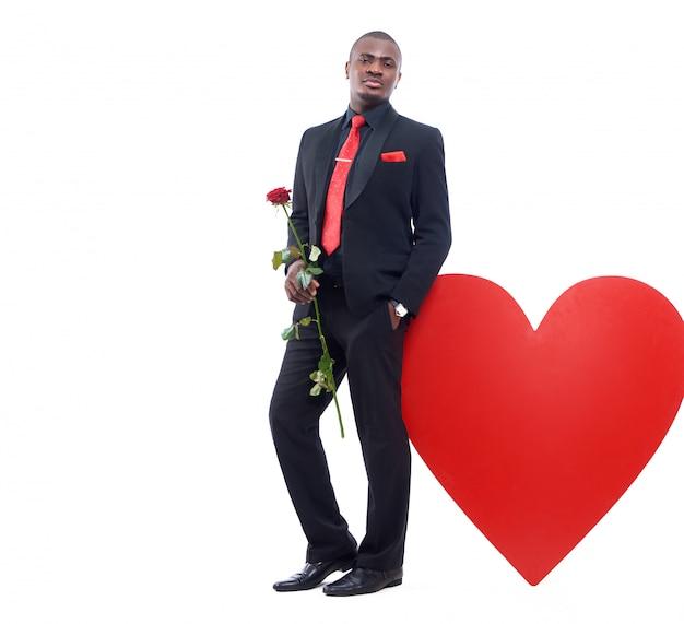 Portret van jonge afrikaanse man in zwarte suite en rode stropdas leunend op grote versierde rood hart