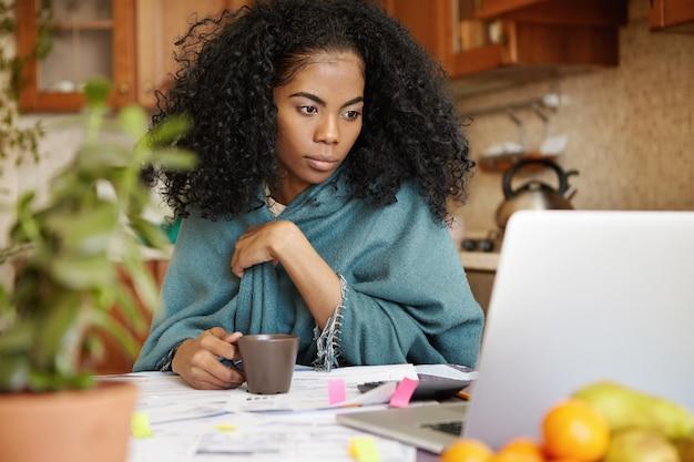 Portret van jonge afrikaanse vrouw die thee drinkt, laptopscherm met gerichte uitdrukking bekijkt