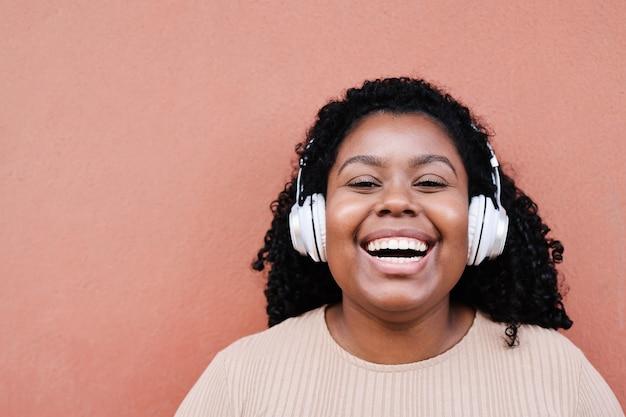 Portret van jonge afrikaanse vrouw luisteren muziek met koptelefoon buiten in de stad
