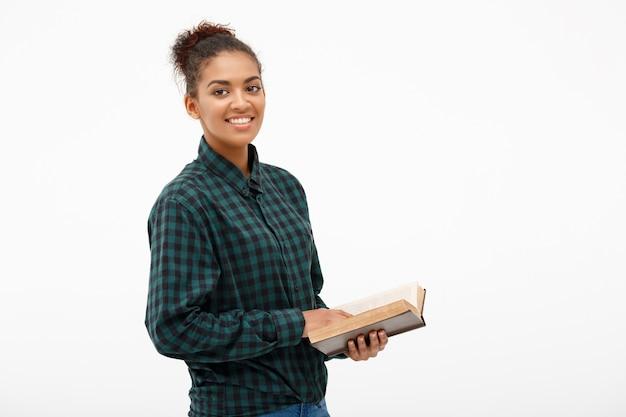 Portret van jonge afrikaanse vrouw met boek op wit.