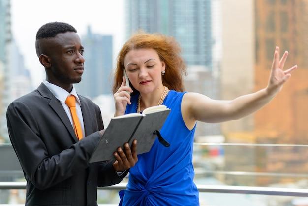 Portret van jonge afrikaanse zakenman en jonge onderneemster met rood haar samen