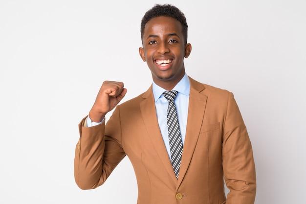 Portret van jonge afrikaanse zakenman met afrohaar in bruin kostuum tegen witte muur