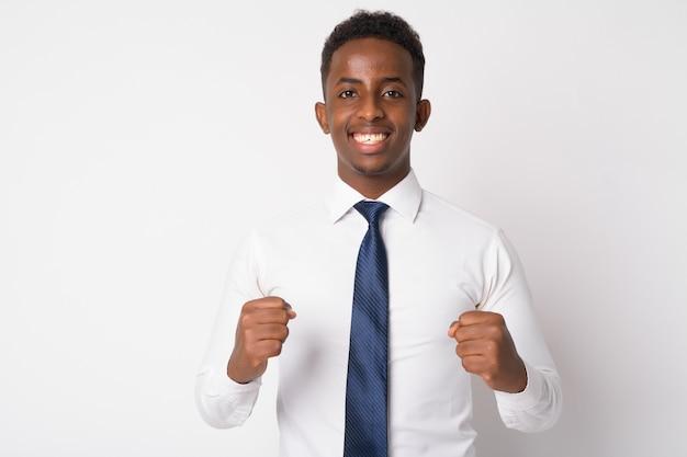 Portret van jonge afrikaanse zakenman met afrohaar tegen witte muur