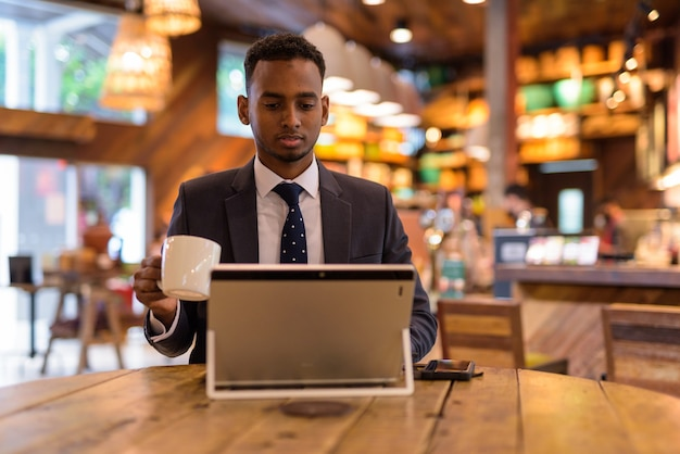 Portret van jonge afrikaanse zakenman ontspannen in coffeeshop
