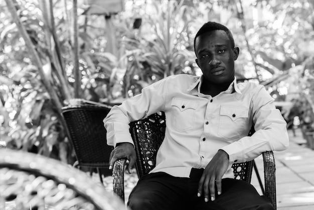 Portret van jonge afrikaanse zakenman ontspannen in de straten buiten in zwart-wit