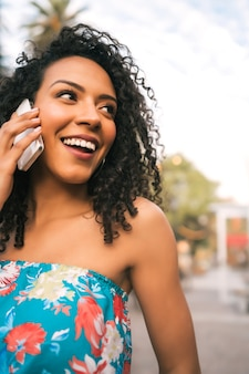 Portret van jonge afro amerikaanse latijns-vrouw praten aan de telefoon buiten in de straat. technologie concept.
