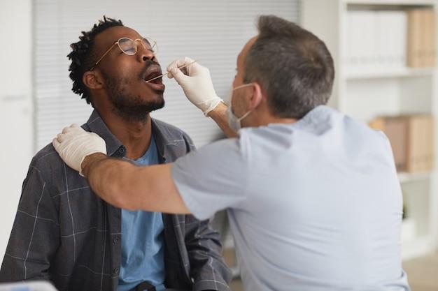 Portret van jonge afro-amerikaanse man die covid-test doet in vaccinatiecentrum of kliniek, kopieer ruimte