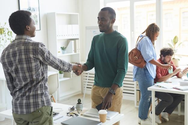 Portret van jonge afro-amerikaanse man gekleed in vrijetijdskleding handen schudden met collega over tafel tijdens de eerste dag op nieuwe baan