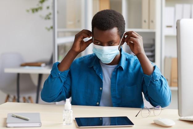 Portret van jonge afro-amerikaanse man gezichtsmasker zetten tijdens het werken aan een bureau in post pandemie kantoor