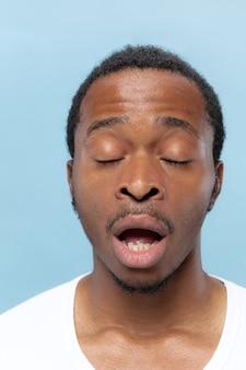 Portret van jonge afro-amerikaanse man in wit overhemd op blauwe achtergrond close-up. menselijke emoties, gezichtsuitdrukking, advertentie, verkoopconcept. een paar seconden voor het niezen. Gratis Foto