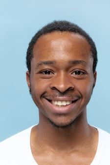 Portret van jonge afro-amerikaanse man in wit overhemd op blauwe muur close-up. menselijke emoties, gezichtsuitdrukking, advertentie, verkoopconcept. ziet er gelukkig uit, lacht, l