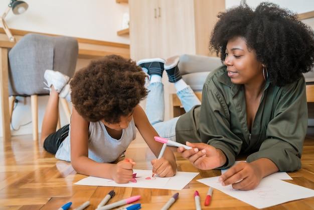 Portret van jonge afro-amerikaanse moeder en zoon tekenen met kleurpotloden op warme vloer thuis. familie concept.