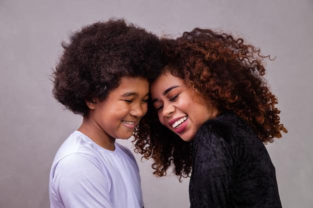 Portret van jonge afro-amerikaanse moeder met peuterzoon. grijze achtergrond. braziliaanse familie.