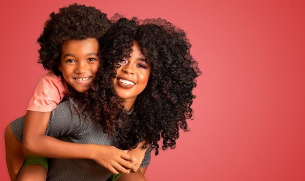 Portret van jonge afro-amerikaanse moeder met peuterzoon. rode achtergrond. braziliaanse familie.