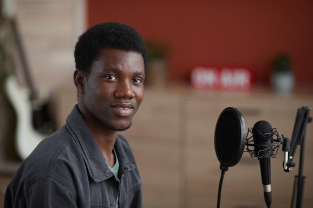 Portret van jonge afro-amerikaanse muzikant camera kijken zittend door microfoon in thuis opnamestudio, kopieer ruimte