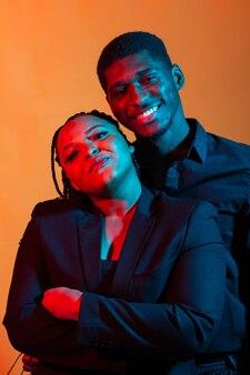 Portret van jonge afro-amerikaanse paar verliefd poseren gekleed in klassieke kleding. neon