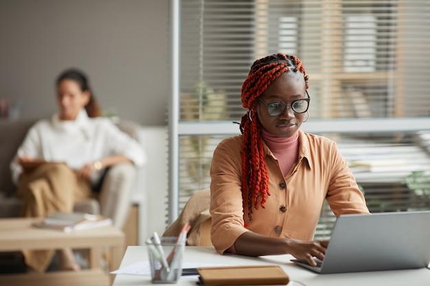 Portret van jonge afro-amerikaanse vrouw met behulp van laptop zittend aan een bureau in kantoor met mensen op de achtergrond, kopieer ruimte