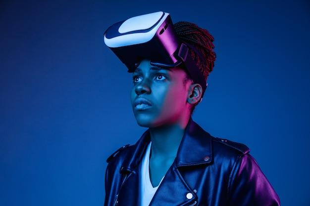 Portret van jonge afro-amerikaanse vrouw spelen in vr-bril in neonlicht op blauw.