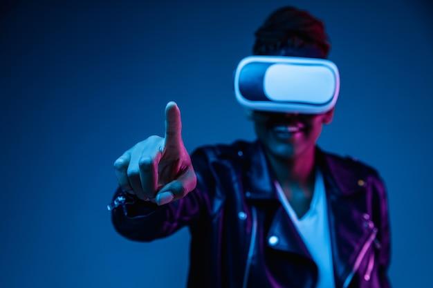 Portret van jonge afro-amerikaanse vrouw spelen in vr-bril in neonlicht op blauwe achtergrond