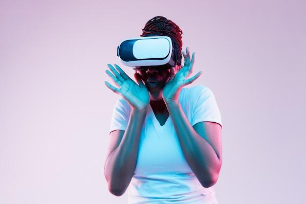 Portret van jonge afro-amerikaanse vrouw spelen in vr-bril in neonlicht op verloop achtergrond. concept van menselijke emoties, gezichtsuitdrukking, moderne gadgets en technologieën. kijk bang.