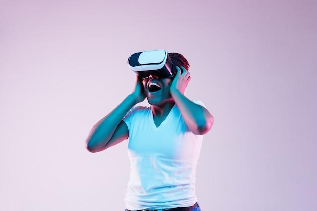 Portret van jonge afro-amerikaanse vrouw spelen in vr-bril in neonlicht op verloop achtergrond. concept van menselijke emoties, gezichtsuitdrukking, moderne gadgets en technologieën. kijk verbaasd.